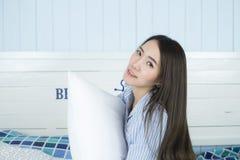 Mujer asiática que celebra la almohada y sonrisas en la cama en su dormitorio Imagen de archivo