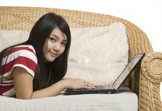 Mujer asiática que coloca usando el ordenador portátil Foto de archivo libre de regalías