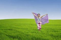 Mujer asiática que corre en campo verde Fotografía de archivo