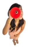 Mujer asiática que echa un vistazo a través de un cono rojo imagen de archivo