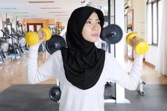 Mujer asiática que ejercita con dos pesas de gimnasia imágenes de archivo libres de regalías