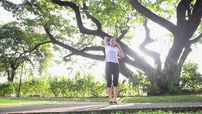 Mujer asiática que ejercita haciendo los enchufes de salto en jardín con el árbol grande y la luz del sol