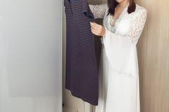 Mujer asiática que elige la ropa en guardarropa fotografía de archivo