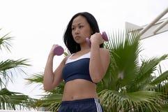 Mujer asiática que encrespa dos pesas de gimnasia púrpuras Imagen de archivo