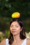 Mujer asiática que equilibra un mango encima de su cabeza Imagen de archivo