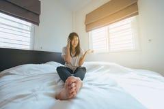 Mujer asiática que habla con su móvil en el dormitorio que siente serio fotos de archivo