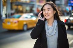 Mujer asiática que habla en el teléfono móvil Imágenes de archivo libres de regalías