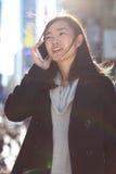 Mujer asiática que habla en el teléfono móvil Imagen de archivo libre de regalías