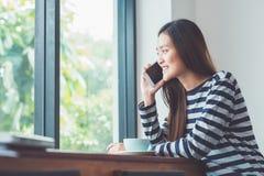 Mujer asiática que habla en el teléfono móvil y que se sienta en el restaura del café Imagen de archivo