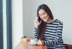 Mujer asiática que habla en el teléfono móvil y que se sienta en el restaura del café Fotografía de archivo