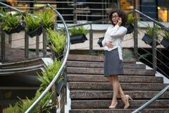 Mujer asiática que habla en el teléfono que se coloca en los pasos al aire libre Fotografía de archivo