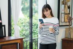 Mujer asiática que habla en la llamada video y la situación del teléfono móvil en c Imagenes de archivo