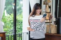 Mujer asiática que habla en la llamada video y la situación del teléfono móvil en c Imágenes de archivo libres de regalías