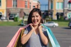 Mujer asiática que hace compras un mercado al aire libre con el fondo de edificios en colores pastel y del cielo azul Fotografía de archivo libre de regalías