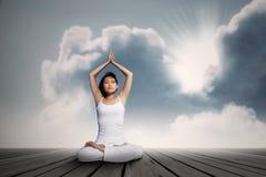 Mujer asiática que hace ejercicio de la yoga debajo del cielo azul Fotografía de archivo