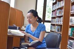 Mujer asiática que hace el libro de la investigación y de lectura en biblioteca imagenes de archivo