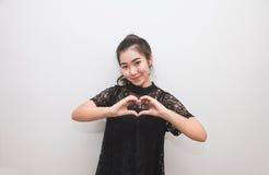 Mujer asiática que hace una muestra con sus manos, lenguaje corporal del corazón Imágenes de archivo libres de regalías
