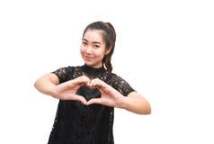 Mujer asiática que hace una muestra del corazón con sus manos Imagen de archivo