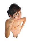 Mujer asiática que intenta ver con la lupa Fotografía de archivo libre de regalías