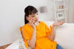 Mujer asiática que invita a smartphone en casa Fotografía de archivo libre de regalías