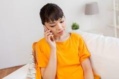 Mujer asiática que invita a smartphone en casa Imagen de archivo