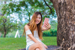 Mujer asiática que juega el selfie del smartphone en un jardín o un parque Fotografía de archivo libre de regalías