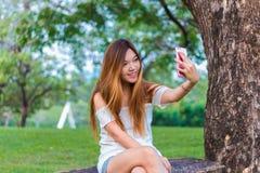 Mujer asiática que juega el selfie del smartphone en un jardín o un parque Fotos de archivo