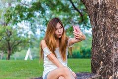Mujer asiática que juega el selfie del smartphone en un jardín o un parque Fotografía de archivo
