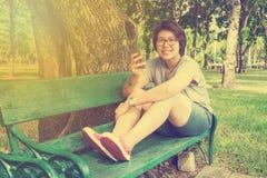 Mujer asiática que juega el smartphone en el parque - efecto del vintage Foto de archivo