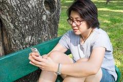 Mujer asiática que juega smartphone en el parque Fotografía de archivo