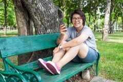 Mujer asiática que juega smartphone en el parque Foto de archivo