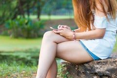 Mujer asiática que juega smartphone en un jardín o un parque Foto de archivo libre de regalías