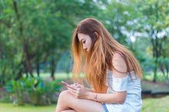 Mujer asiática que juega smartphone en un jardín o un parque Fotografía de archivo