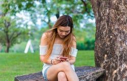 Mujer asiática que juega smartphone en un jardín o un parque Fotografía de archivo libre de regalías