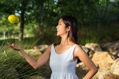 Mujer asiática que lanza un mango u en el aire Fotos de archivo libres de regalías