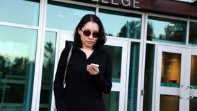 Mujer asiática que lee el mensaje de teléfono móvil metrajes