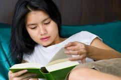 Mujer asiática que lee un libro Fotos de archivo