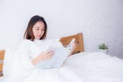 Mujer asiática que lee un libro y que sonríe en dormitorio Foto de archivo