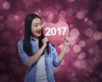 Mujer asiática que lleva a cabo el corazón rojo con el número 2017 Fotografía de archivo libre de regalías