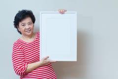 Mujer asiática que lleva a cabo el marco blanco vacío en el tiro del estudio, SP Fotografía de archivo libre de regalías