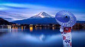 Mujer asiática que lleva el kimono tradicional japonés en la montaña de Fuji, lago Kawaguchiko en Japón fotografía de archivo