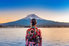 Mujer asiática que lleva el kimono tradicional japonés en la montaña de Fuji Puesta del sol en el lago Kawaguchiko en Japón imagen de archivo
