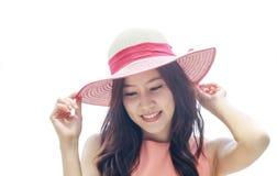 Mujer asiática que lleva el sombrero de paja rosado con la expresión de feliz foto de archivo libre de regalías