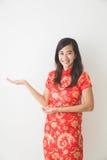 Mujer asiática que lleva la presentación del vestido del chino tradicional imagenes de archivo