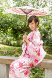 Mujer asiática que lleva un yukata en jardín del estilo japonés Foto de archivo