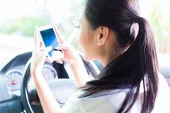 Mujer asiática que manda un SMS mientras que conduce el coche Imagenes de archivo