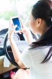 Mujer asiática que manda un SMS mientras que conduce el coche Foto de archivo