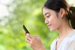 Mujer asiática que mecanografía en smartphone Fotografía de archivo