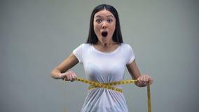 Mujer asiática que mide su cintura, satisfecha con resultados del entrenamiento y de la dieta, ajuste almacen de video