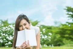 Mujer asiática que miente en campo de hierba con el libro blanco en el parque Fotografía de archivo libre de regalías
